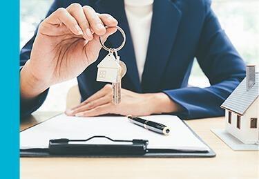 Agent z biura Properton trzyma klucze do nieruchomości w Warszawie