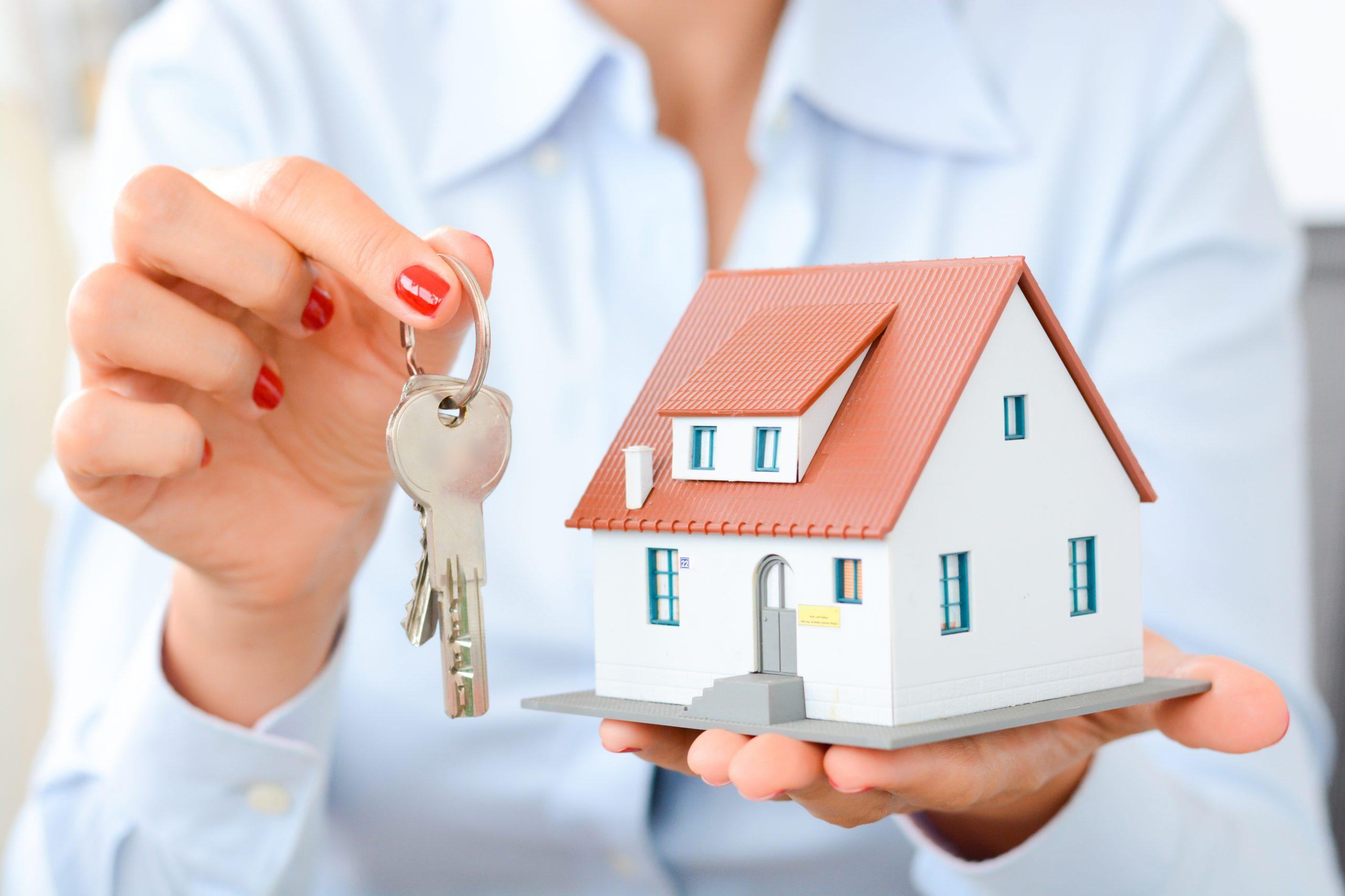 Agent trzyma klucze i makiete nieruchomości do zakupu prz biuro Properton